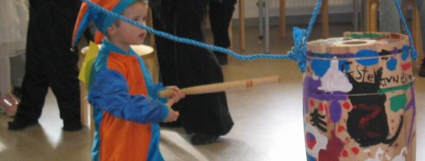 Dreng udklædt som nar slår katten af tønden